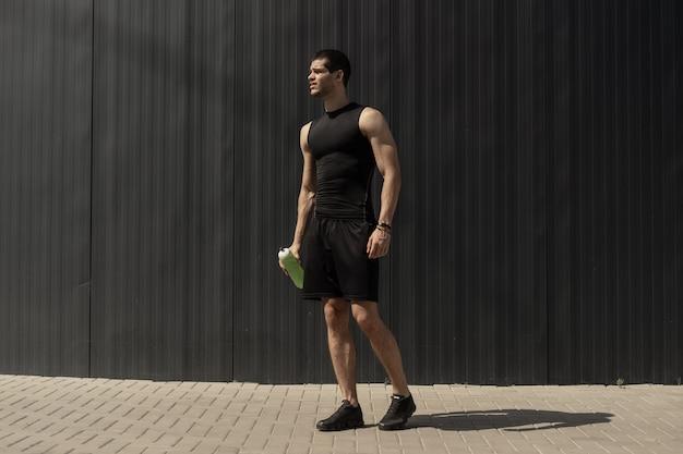 Спортивный современный молодой человек позирует на серой металлической стене Бесплатные Фотографии
