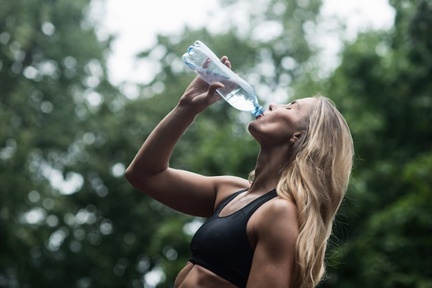 Athletic muscular girl drinking water after training the concept of a healthy lifestyle Premium Photo