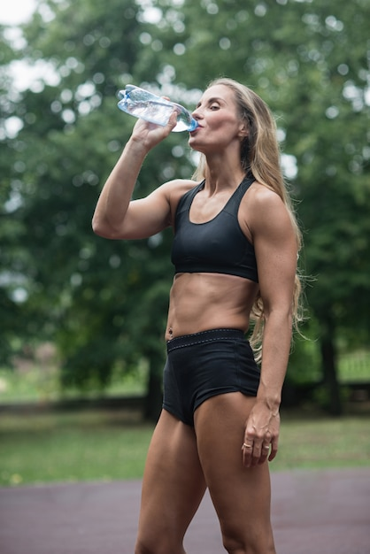 Athletic muscular girl drinking water after training Premium Photo