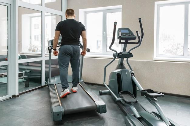 Athletic muscular man running on treadmills Premium Photo