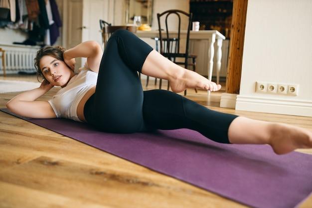 운동 근육질의 젊은 여성이 머리 뒤에 손을 대고 누워 자전거 크런치를하고 팔꿈치를 무릎쪽으로 가져오고 복근과 코어 근육을 운동합니다. 무료 사진