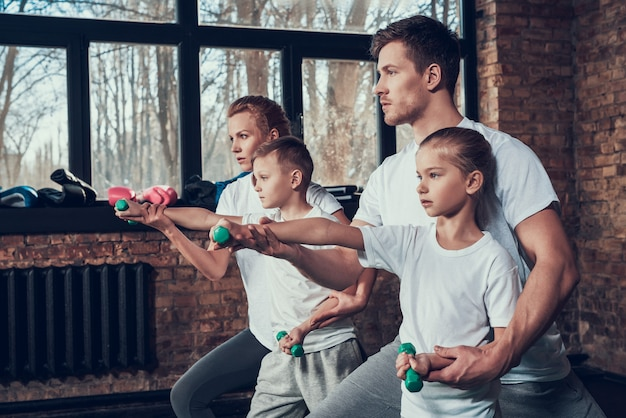 Athletic serious family exercises with dumbbells in the gym. Premium Photo
