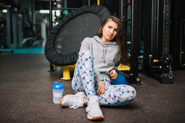 Athletic serious woman sitting near bottle in gym Free Photo
