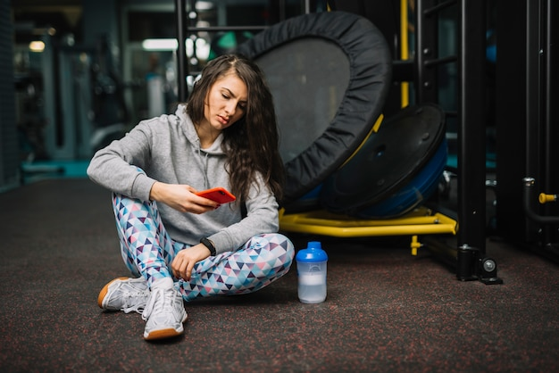 Athletic serious woman with smartphone sitting near bottle in gym Free Photo