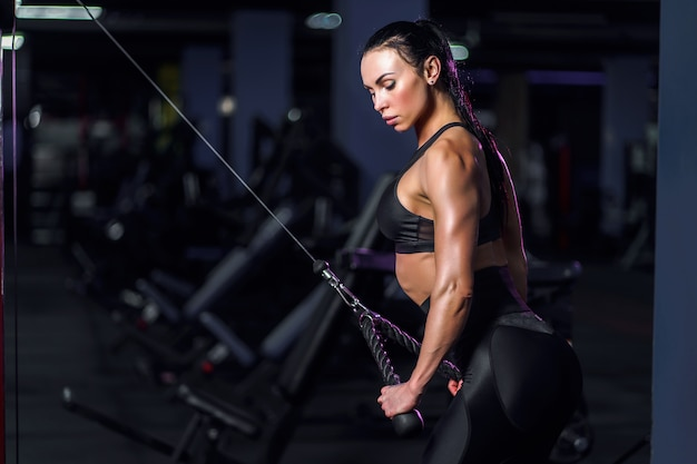 Athletic sexy woman doing exercise using machine in gym - side view Premium Photo
