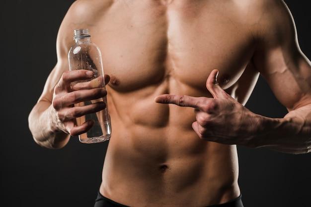 Athletic shirtless man pointing at water bottle Free Photo