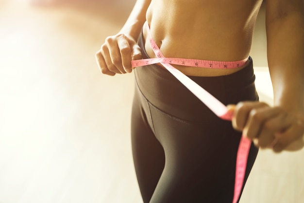 Athletic slim woman measuring her waist with measure tape Premium Photo