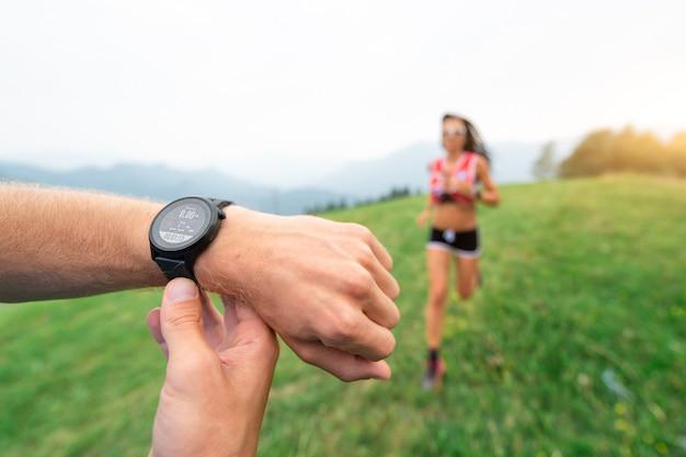 Спортивный тренер держит секундомер во время тренировки девушки, бегущей на природе Premium Фотографии
