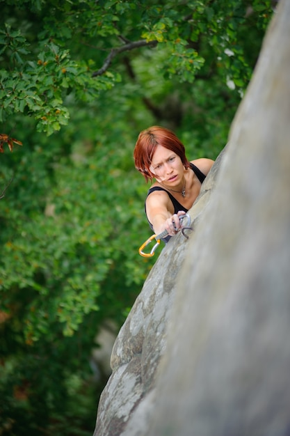 Athletic woman climbing steep cliff wall in summer time Premium Photo