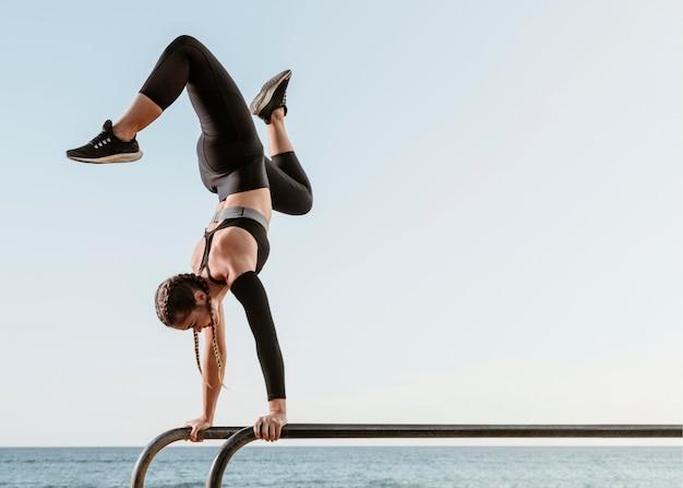 Спортивная (ый) женщина делает фитнес-тренировку снаружи на пляже Бесплатные Фотографии