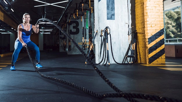An athletic woman exercising wit battle ropes in fitness club Free Photo