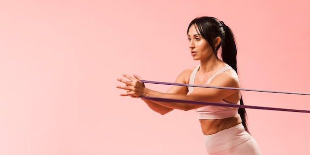 Athletic woman in gym outfit pulling resistance band Premium Photo
