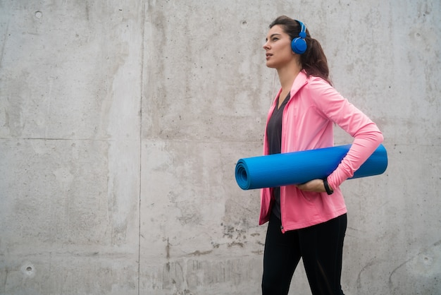 Donna atletica che tiene una stuoia di addestramento. Foto Gratuite
