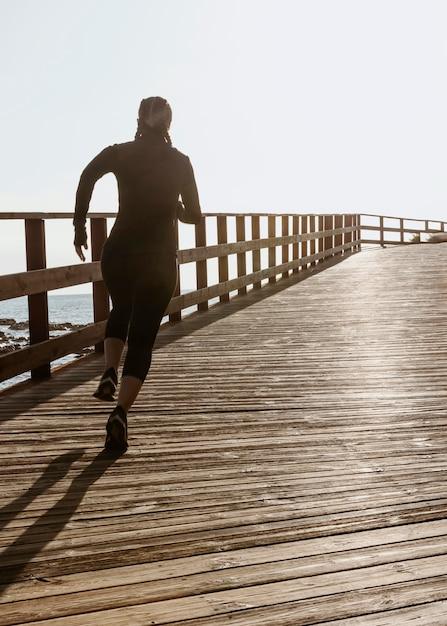 Donna atletica che pareggia sulla spiaggia con lo spazio della copia Foto Gratuite