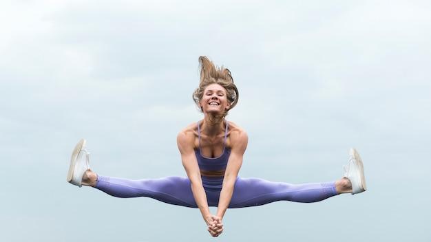 Athletic woman jumping long shot Free Photo