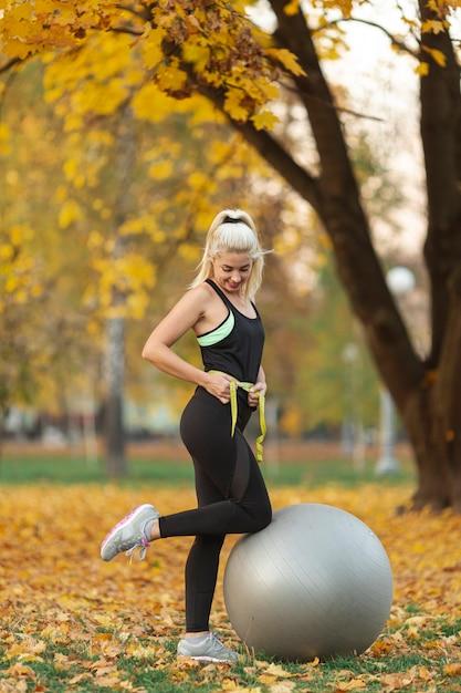 Donna atletica che misura la sua vita Foto Gratuite