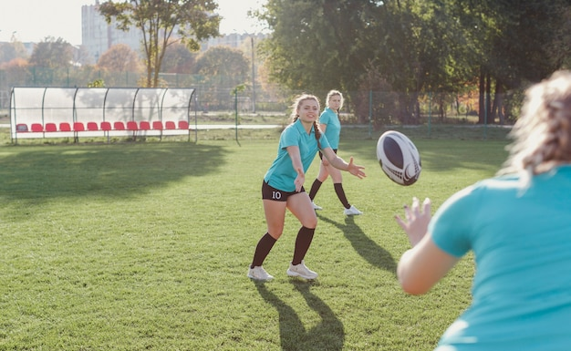 Athletic woman passing a rugby ball Free Photo
