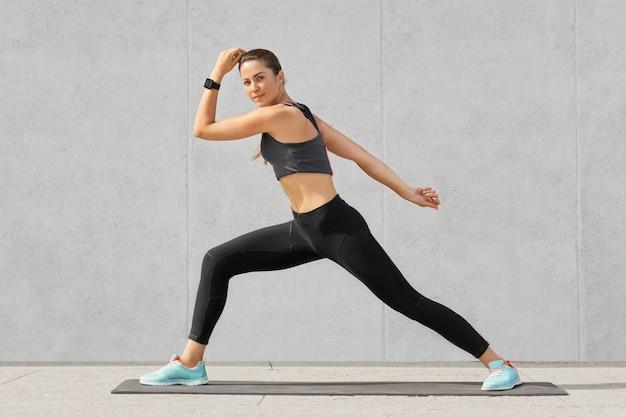 スポーツ女性がヨガの練習、広いステップを踏む、良い柔軟性を示す、灰色に対するポーズ 無料写真