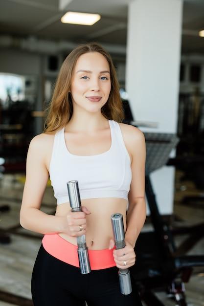 Donna atletica pompare i muscoli con manubri in palestra Foto Gratuite