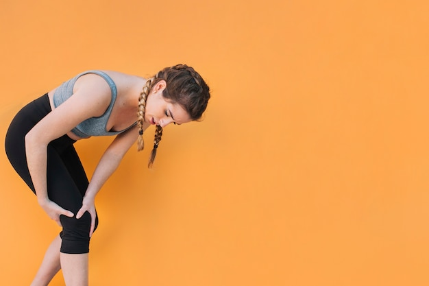 Athletic woman touching hurting knee Free Photo