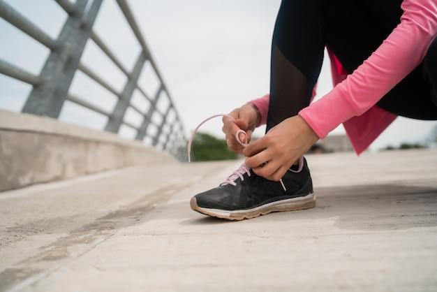 靴ひもを結ぶ運動の女性。 Premium写真