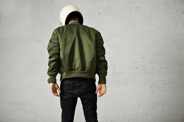 スキニージーンズ、緑のボンバージャケット、白いオートバイのヘルメットの白い、後ろの肖像画に分離された運動の若いモデル 無料写真