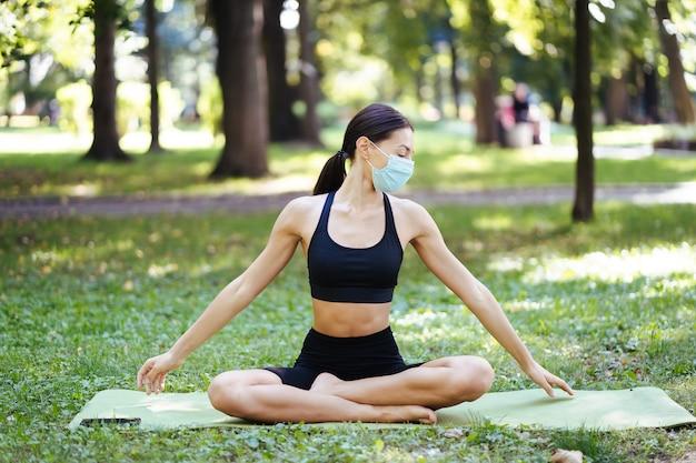 의료 보호 마스크에 운동 젊은 여자, 아침에 공원에서 요가, 요가 매트에 여성의 훈련 무료 사진