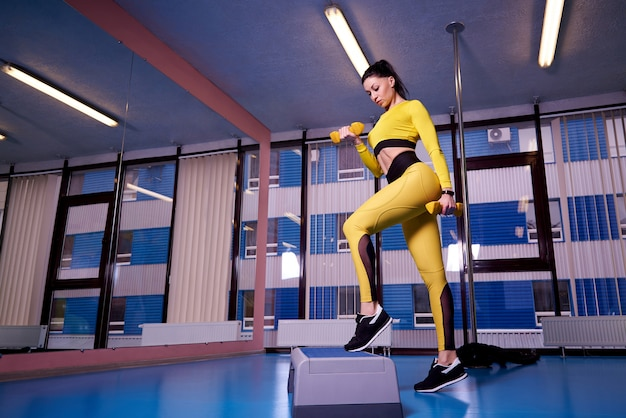 Athletic young woman using step platform in the gym. Premium Photo