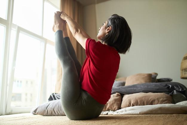 Спортивная молодая женщина с сильным подтянутым телом, практикующая йогу в спальне, сидя перед напряженной растяжкой Бесплатные Фотографии