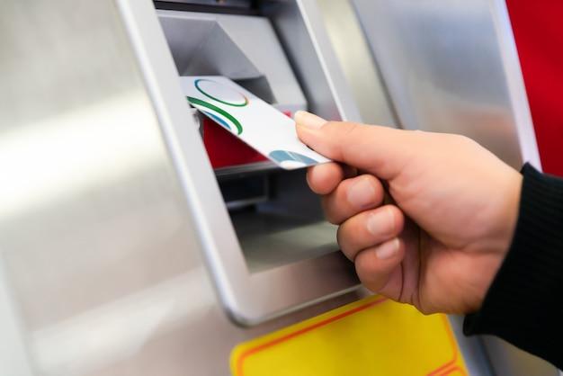 Atmを使用して、クレジットカードを持つ男の手。彼のクレジットカードでatmマシンを使用している人。 Premium写真