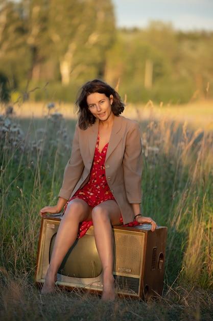自然の中で古いレトロなテレビの上に座って赤いドレスを着た若い女性の大気の肖像画。 Premium写真