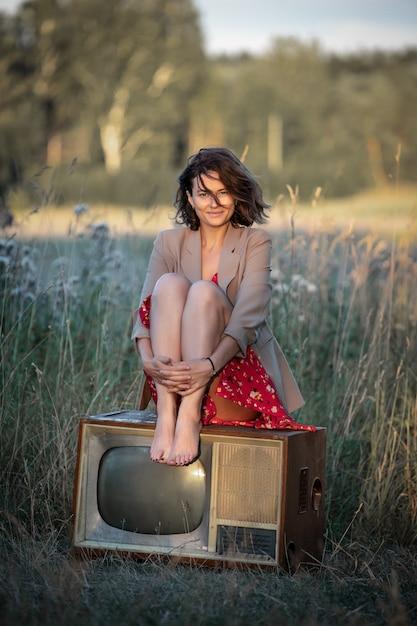 古いレトロなテレビの上に座って赤いドレスを着た若い女性の大気の肖像画 Premium写真