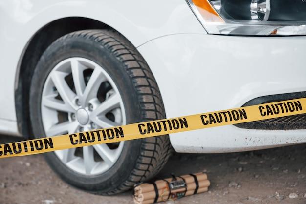 Попытка предотвращена. опасное взрывчатое вещество возле колеса современного белого автомобиля. желтая предупреждающая лента спереди Бесплатные Фотографии