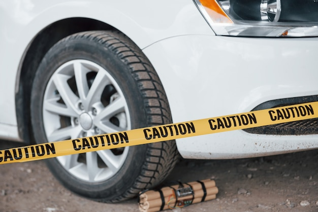 Attempt is prevented. dangerous explosive near the wheel of modern white car. yellow caution tape in front Free Photo
