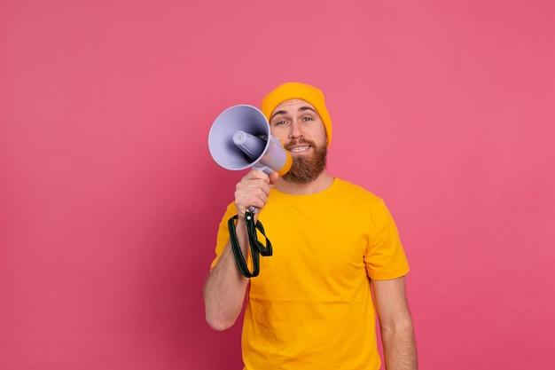 Attenzione! uomo europeo che grida nel megafono su sfondo rosa Foto Gratuite