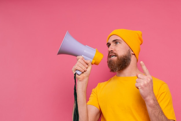 Attention! european man shouting in megaphone on pink background Free Photo
