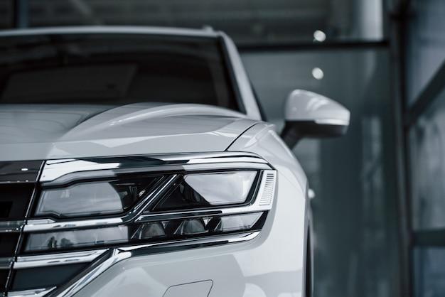 詳細への注意。昼間に屋内に駐車したモダンで豪華な白い車のパーティクルビュー 無料写真