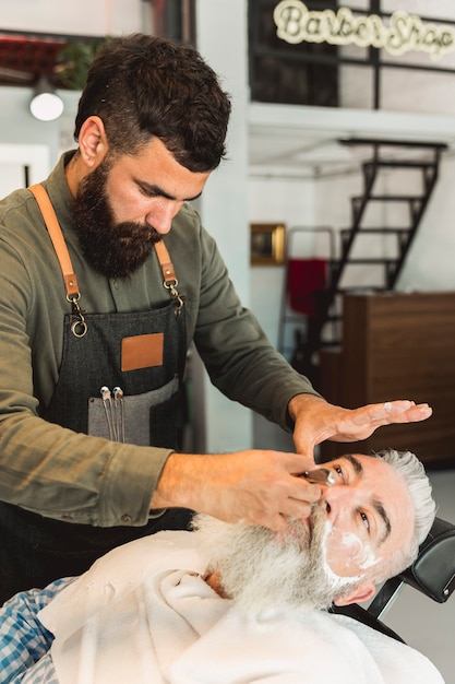 Attentive barber shaving beard to client in barber shop Free Photo