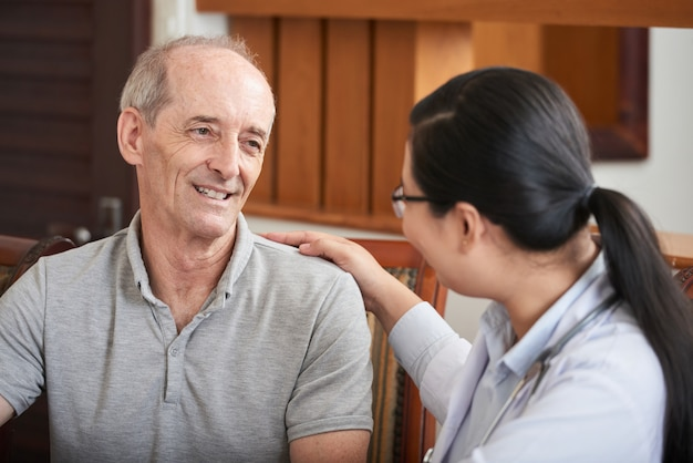 Attentive doctor soothing senior patient Free Photo