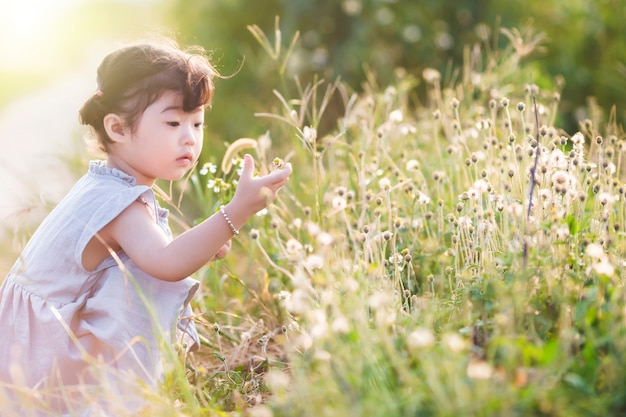 Attentive girl touching flowers Free Photo