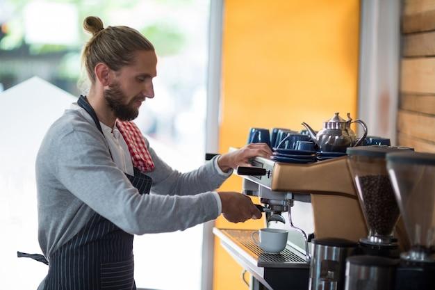 Внимательный официант делает чашку кофе Premium Фотографии