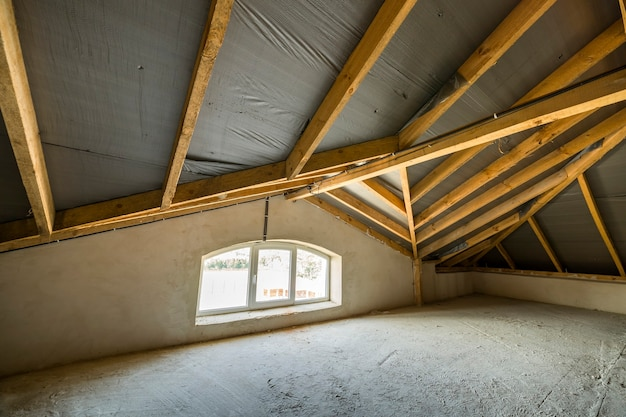 Attic of a building with wooden beams of a roof structure and a small window. Premium Photo