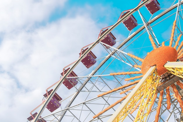 Attraction ferris wheel on a background of blue sky with clouds Premium Photo
