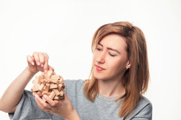 木製のパズルと混同している魅力的な24歳のビジネス女性。 無料写真