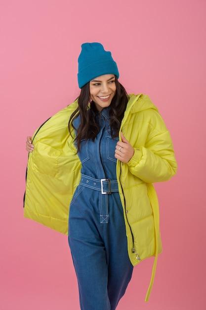 밝은 노란색 색상의 화려한 겨울 다운 재킷, 따뜻한 코트 패션 트렌드에 분홍색 벽에 포즈 매력적인 활성 여자 모델 무료 사진
