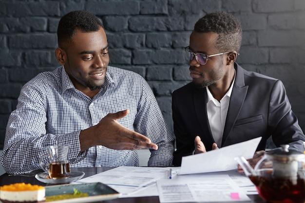 メガネと紙を保持しているスーツで魅力的なアフリカの実業家 無料写真