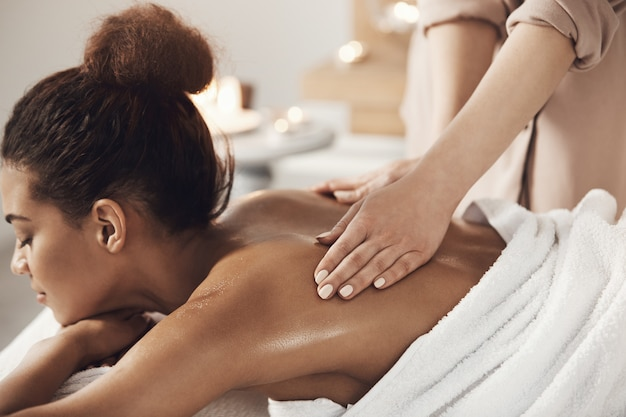 Attractive african woman having massage relaxing in spa salon. closed eyes. Free Photo