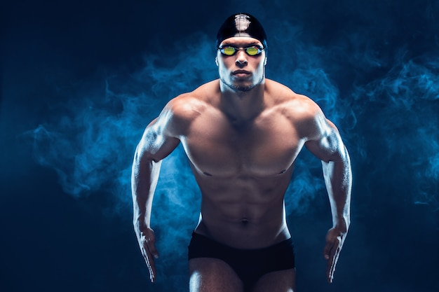 Привлекательный и мускулистый пловец. съемка студии молодого без рубашки спортсмена на черной предпосылке. человек в очках Premium Фотографии