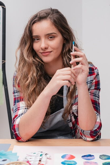 Attractive artist looking at camera holding paintbrush Free Photo