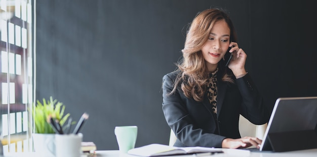 Attractive asian businesswoman speaking on the phone with customer Premium Photo